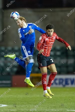Gillingham FC midfielder Stuart O'Keefe (4) wins a header from Lincoln City Midfielder Brennan Johnson (On loan from Nottingham Forest) (20) during the EFL Sky Bet League 1 match between Lincoln City and Gillingham at Sincil Bank, Lincoln