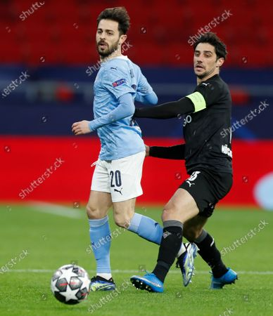 Manchester City's Bernardo Silva, left, and Moenchengladbach's Lars Stindl battle for the ball during the Champions League round of 16 second leg soccer match between Manchester City and Borussia Moenchengladbach at the Puskas Arena in Budapest, Hungary