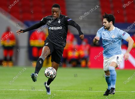 Moenchengladbach's Denis Zakaria and Manchester City's Ilkay Gundogan, right, battle for the ball during the Champions League round of 16 second leg soccer match between Manchester City and Borussia Moenchengladbach at the Puskas Arena in Budapest, Hungary