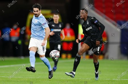 Manchester City's Ilkay Gundogan, left, kicks the ball past Moenchengladbach's Denis Zakaria during the Champions League round of 16 second leg soccer match between Manchester City and Borussia Moenchengladbach at the Puskas Arena in Budapest, Hungary