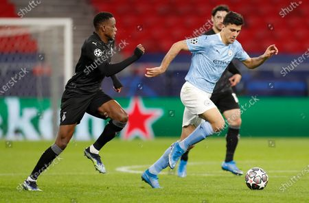 Manchester City's Rodrigo, right, and Moenchengladbach's Denis Zakaria compete for the ball during the Champions League round of 16 second leg soccer match between Manchester City and Borussia Moenchengladbach at the Puskas Arena in Budapest, Hungary
