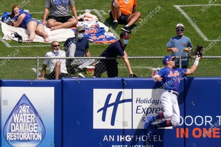 New York Mets center fielder Brandon Nimmo catches a fly ball at the fence hit by Houston Astros' Alex Bregman during the fourth inning of a spring training baseball game, in Port St. Lucie, Fla