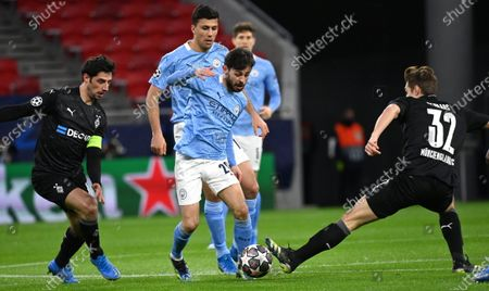 Lars Stindl of Moenchengladbach (L), Bernardo Silva (C) of Manchester City are challenged by Florian Neuhaus (R) during the UEFA Champions League round of 16 second leg soccer match between Manchester City and Borussia Moenchengladbach in the Puskas Ferenc Arena in Budapest, Hungary, 16 March 2021.