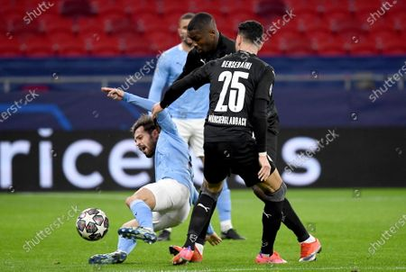 Bernardo Silva (L) of Manchester City vies for the ball with Denis Zakaria and Ramy Bensebani (R) during the UEFA Champions League round of 16 second leg soccer match between Manchester City and Borussia Moenchengladbach in the Puskas Ferenc Arena in Budapest, Hungary, 16 March 2021.