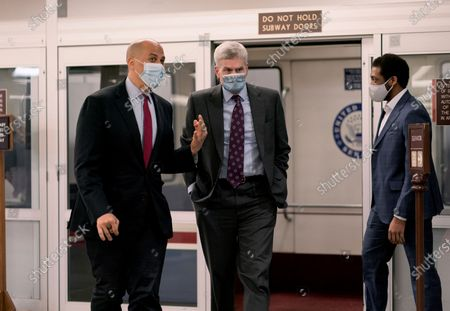 Sen. Cory Booker, D-N.J., left, talks with Sen. Bill Cassidy, R-La., as they arrive as the Senate holds votes on nominees for the Biden administration, at the Capitol in Washington
