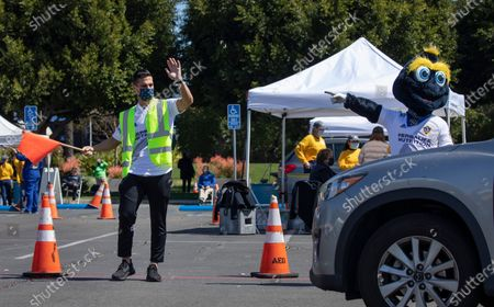 Galaxy midfielder Sebastian Lletget and team mascot Cozmo help direct traffic on Tuesday, March 16, 2021 at Dignity Health Sports Park in Carson, CA, the home of Galaxy soccer, that was turned into a COVID vaccination site.