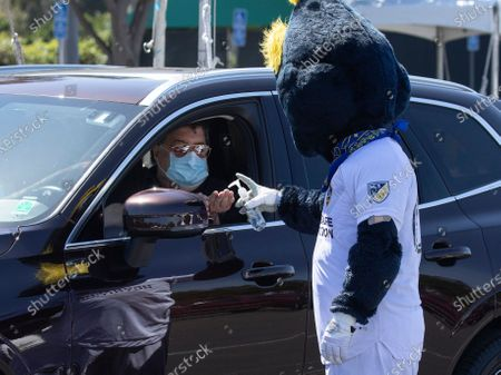 Galaxy mascot Cozmo offers a shot of hand sanitizer to a visitor getting a second COVID vaccine shot at Dignity Health Sports Park in Carson, CA on Tuesday, March 16, 2021. The parking lot at the home of Galaxy soccer was turned into a COVID vaccination site.