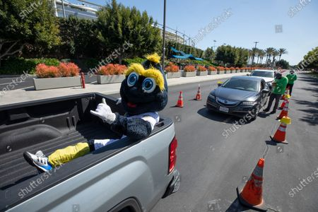 Galaxy mascot Cozmo hitches a ride in the back of a visiting pickup truck during COVID vaccination at Dignity Health Sports Park in Carson, CA on Tuesday, March 16, 2021. The parking lot at the home of Galaxy soccer was turned into a COVID vaccination site.