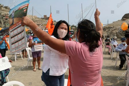 Wearing a mask to curb the spread of the new coronavirus, Presidential candidate and daughter of imprisoned ex-President Alberto Fujimori, Keiko Fujimori, of the Popular Force party, greets a supporter as she campaigns in San Juan de Lurigancho on the outskirts of Lima, Peru, . Peru's general election is set for April 11