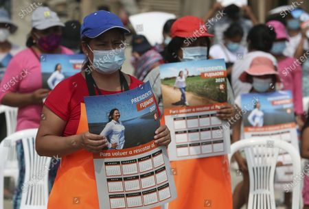 Wearing masks to curb the spread of the new coronavirus, supporters of Presidential candidate and daughter of imprisoned ex-President Alberto Fujimori, Keiko Fujimori, of the Popular Force party, hold calendars sporting her photo as she campaigns in San Juan de Lurigancho on the outskirts of Lima, Peru, . Peru's general election is set for April 11