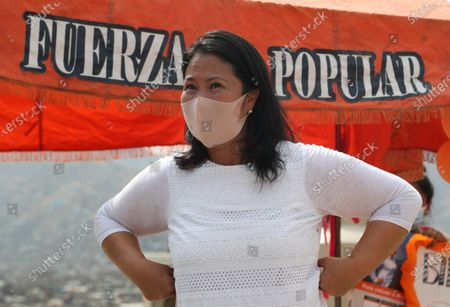 Wearing a mask to curb the spread of the new coronavirus, presidential candidate and daughter of imprisoned ex-President Alberto Fujimori, Keiko Fujimori, of the Popular Force party, looks on as she campaigns in San Juan de Lurigancho on the outskirts of Lima, Peru, . Peru's general election is set for April 11
