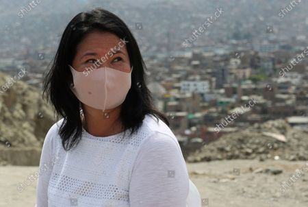Wearing a mask to curb the spread of the new coronavirus, presidential candidate and daughter of imprisoned ex-President Alberto Fujimori, Keiko Fujimori, of the Popular Force party, listens to supporters as she campaigns in San Juan de Lurigancho on the outskirts of Lima, Peru, . Peru's general election is set for April 11