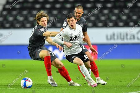 Jason Knight of Derby County `battles with Mads Bech Sorensen and Winston Reid of Brentford during the Sky Bet Championship match between Derby County and Brentford at the Pride Park, Derby on Tuesday 16th March 2021.