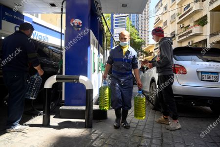 Lebanese men buy fuel at a gas station in Beirut, Lebanon, 17 March 2021. The Lebanese Ministry of Energy and Water on 17 March 2021 increased fuel prices, raising the petrol price to 1,945 LP (1.28 US dollar) per liter. The dollar exchange rate on the parallel market has topped 14,500 Lebanese pounds a spike from the pegged rate of 1,507.