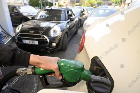 Stock Photo of A gas station attendant fills a car in Beirut, Lebanon, 17 March 2021. The Lebanese Ministry of Energy and Water on 17 March 2021 increased fuel prices, raising the petrol price to 1,945 LP (1.28 US dollar) per liter. The dollar exchange rate on the parallel market has topped 14,500 Lebanese pounds a spike from the pegged rate of 1,507.
