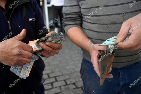 An attendant (L) counts Lebanese pounds next to a customer at a gas station in Beirut, Lebanon, 17 March 2021.  The Lebanese Ministry of Energy and Water on 17 March 2021 increased fuel prices, raising the petrol price to 1,945 LP (1.28 US dollar) per liter. The dollar exchange rate on the parallel market has topped 14,500 Lebanese pounds a spike from the pegged rate of 1,507.