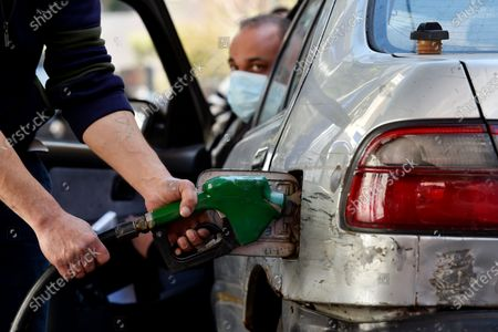 A gas station attendant fills a car in Beirut, Lebanon, 17 March 2021. The Lebanese Ministry of Energy and Water on 17 March 2021 increased fuel prices, raising the petrol price to 1,945 LP (1.28 US dollar) per liter. The dollar exchange rate on the parallel market has topped 14,500 Lebanese pounds a spike from the pegged rate of 1,507.