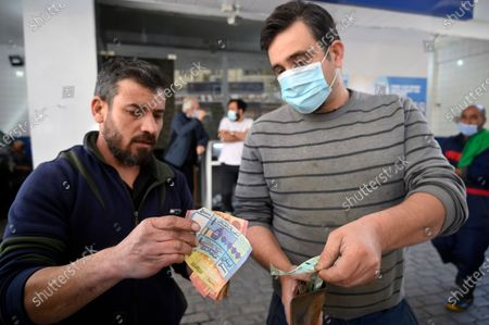 Stock Picture of An attendant (L) counts Lebanese pounds next to a customer at a gas station in Beirut, Lebanon, 17 March 2021. The Lebanese Ministry of Energy and Water on 17 March 2021 increased fuel prices, raising the petrol price to 1,945 LP (1.28 US dollar) per liter. The dollar exchange rate on the parallel market has topped 14,500 Lebanese pounds a spike from the pegged rate of 1,507.
