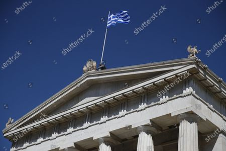 Worker adjusts the Greek flag atop of the old National Library building in Athens, . Greece launched a 30-year government bond auction on Wednesday, hoping to take advantage of low interest rates and improve its debt profile, in part to offset the impact of the pandemic on the country's public finances