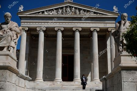 Woman leaves the Athens Academy building on . Greece launched a 30-year government bond auction on Wednesday, hoping to take advantage of low interest rates and improve its debt profile, in part to offset the impact of the pandemic on the country's public finances