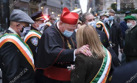 New York Cardinal Timothy M. Dolan (C) prays with a woman outside of St. Patrick's Cathedral before a St. Patrick's Day mass in New York, New York, USA, 17 March 2021. New York City normally hosts one of the largest St. Patrick's Day parades but plans for large celebrations are still being severely limited due to the coronavirus pandemic.