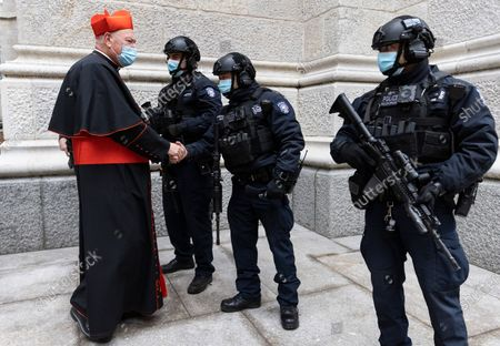 New York Cardinal Timothy M. Dolan (L) greets heavily armed members of the New York City police department guarding St. Patrick's Cathedral before a St. Patrick's Day mass in New York, New York, USA, 17 March 2021. New York City normally hosts one of the largest St. Patrick's Day parades but plans for large celebrations are still being severely limited due to the coronavirus pandemic.