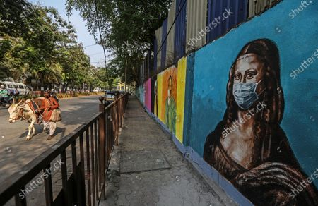 People walks past the wall showing a graffiti of Italian artist Leonardo da Vinci's Mona Lisa wearing a face mask, in Mumbai, India, 17 March 2021. India has recorded its highest two-day spike this year with over 20,000 Covid-19 cases reported from all over India.