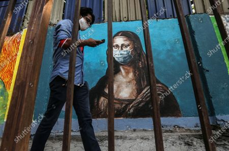 Stock Photo of An Indian man walks past a wall showing a graffiti of Italian artist Leonardo da Vinci's Mona Lisa wearing a face mask, in Mumbai, India, 17 March 2021. India has recorded its highest two-day spike this year with over 20,000 Covid-19 cases reported from all over India.