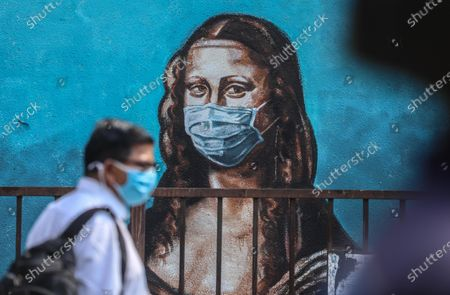 An Indian man walks past a wall showing a graffiti of Italian artist Leonardo da Vinci's Mona Lisa wearing a face mask, in Mumbai, India, 17 March 2021. India has recorded its highest two-day spike this year with over 20,000 Covid-19 cases reported from all over India.