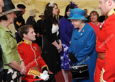 Stock Image of Queen Elizabeth II speaks with Lieutenant Garth Banks from the Grenadier Guards after presenting the regiment with their new colours