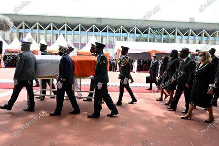 Stock Image of Ivorian President Alassane Ouattara (2nd R) and his wife Dominique Folloroux-Ouattara (R) and Hamed Bakayoko's children walk behind the coffin of Ivory Coast's late prime minister Hamed Bakayoko during his official tribute ceremony at the presidential palace in Abidjan, Ivory Coast, 17 March 2021. Hamed Bakayoko died on 10 March 2021 following cancer treatment in a German hospital.