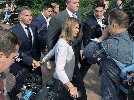 """Stock Photo of Lori Loughlin departs federal court with her husband, clothing designer Mossimo Giannulli, left, in Boston, after a hearing in a nationwide college admissions bribery scandal. A new documentary about the college admissions scandal, """"Operation Varsity Blues: The College Admissions Scandal,"""" premiering Wednesday on Netflix"""