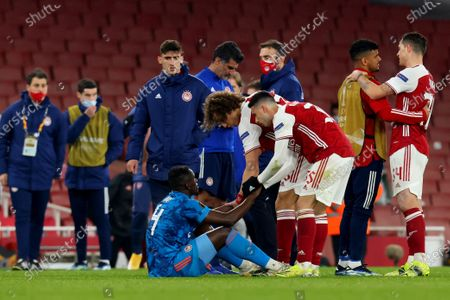 Gabriel Martinelli and David Luiz of Arsenal speak to a dejected Mady Camara of Olympiakos after the 3-2 loss on aggregate; Emirates Stadium, London, England; UEFA Europa League Football, Arsenal versus Olympiacos.