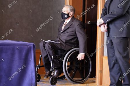 Masked Texas Gov Greg Abbott arrives for a news conferenced about migrant children detentions, in Dallas
