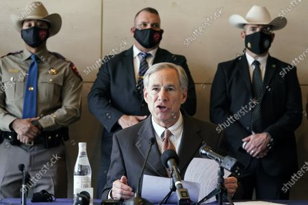 Masked Texas Gov Greg Abbott speaks at a news conferenced about migrant children detentions, in Dallas