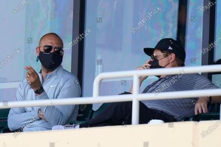 Miami Marlins CEO Derek Jeter, left, watches a spring training baseball game between the Miami Marlins and New York Mets, in Jupiter, Fla
