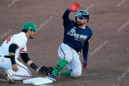 Atlanta Braves' Ender Inciarte is tagged out at third base by Baltimore Orioles third baseman Rio Ruiz (14) as he tries to advance on a Pablo Sandoval base hit during the fifth inning of a spring training baseball game, in Sarasota, Fla