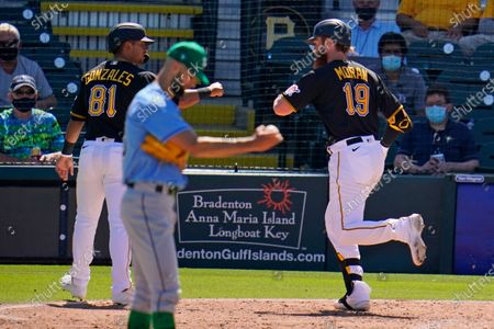 Pittsburgh Pirates' Colin Moran (19) celebrates with Nick Gonzalez (81) after hitting a two-run home run off Tampa Bay Rays pitcher Nick Anderson, center, during the fifth inning of a spring training exhibition baseball game in Bradenton, Fla