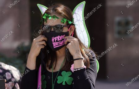 Dressed in green for St. Patrick's Day, Britney Spears fan Kiki Norberto of Phoenix adjusts her mask outside a court hearing concerning the pop singer's conservatorship at the Stanley Mosk Courthouse, in Los Angeles. Attorneys for Spears and lawyers for her father Jamie Spears jointly asked the judge to delay an accounting and status report on the conservatorship until April 27
