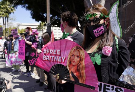 Britney Spears supporter Kiki Norberto holds a hand fan outside a court hearing concerning the pop singer's conservatorship at the Stanley Mosk Courthouse, in Los Angeles. Attorneys for Spears and lawyers for her father Jamie Spears jointly asked the judge to delay an accounting and status report on the conservatorship until April 27