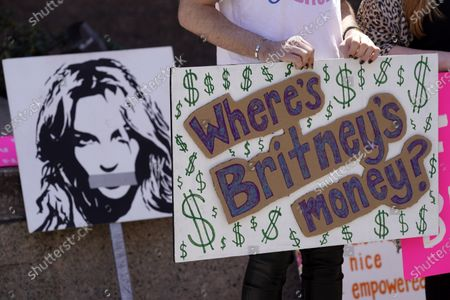Britney Spears supporter holds a sign near a portrait of her outside a court hearing concerning the pop singer's conservatorship at the Stanley Mosk Courthouse, in Los Angeles. Attorneys for Spears and lawyers for her father Jamie Spears jointly asked the judge to delay an accounting and status report on the conservatorship until April 27