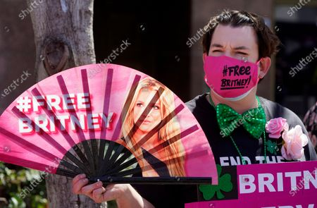 Britney Spears supporter Dustin Strand of Phoenix holds a hand fan outside a court hearing concerning the pop singer's conservatorship at the Stanley Mosk Courthouse, in Los Angeles. Attorneys for Spears and lawyers for her father Jamie Spears jointly asked the judge to delay an accounting and status report on the conservatorship until April 27