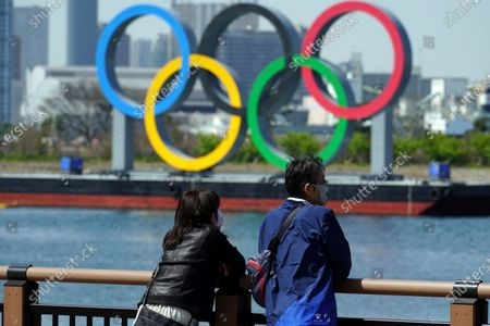"""Man and a woman stand with a backdrop of the Olympic rings floating in the water in the Odaiba section, in Tokyo. Tokyo Olympics creative director Hiroshi Sasaki is resigning after making demeaning comments about Naomi Watanabe, a well-known female celebrity. Sasaki who was in charge of the opening and closing ceremonies for the Olympics, told planning staff members last year that Watanabe could perform in the ceremony as an """"Olympig"""
