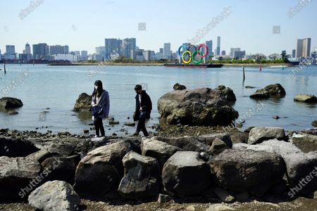 """Man and a woman walk on rocks with a backdrop of the Olympic rings floating in the water in the Odaiba section, in Tokyo. Tokyo Olympics creative director Hiroshi Sasaki is resigning after making demeaning comments about Naomi Watanabe, a well-known female celebrity. Sasaki who was in charge of the opening and closing ceremonies for the Olympics, told planning staff members last year that Watanabe could perform in the ceremony as an """"Olympig"""
