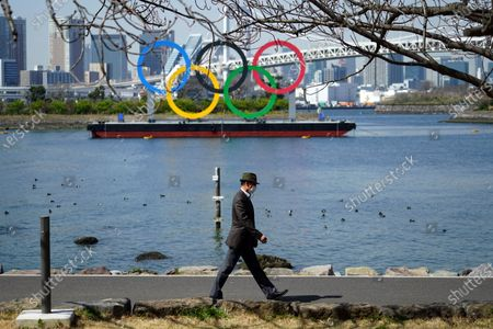 """Man walks with a backdrop of the Olympic rings floating in the water in the Odaiba section, in Tokyo. Tokyo Olympics creative director Hiroshi Sasaki is resigning after making demeaning comments about Naomi Watanabe, a well-known female celebrity. Sasaki who was in charge of the opening and closing ceremonies for the Olympics, told planning staff members last year that Watanabe could perform in the ceremony as an """"Olympig"""