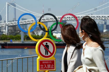 """Women walk by a """"no trespassing"""" sign at a park with a backdrop of the Olympic rings floating in the water in the Odaiba section, in Tokyo. Tokyo Olympics creative director Hiroshi Sasaki is resigning after making demeaning comments about Naomi Watanabe, a well-known female celebrity. Sasaki who was in charge of the opening and closing ceremonies for the Olympics, told planning staff members last year that Watanabe could perform in the ceremony as an """"Olympig"""