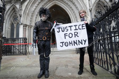 Johnny Depp supporters hold a banner outside the High Court in London, . Johnny Depp's bid to overturn a damning ruling that he assaulted his ex-wife Amber Heard and put her in fear for her life will be considered by the Court of Appeal on Thursday