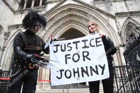Fans in costume display a banner in support of US actor Johnny Depp outside the Royal Courts of Justice in London, Britain, 18 March 2021. US actor Johnny Depp is appealing the verdict after he lost his case when suing The Sun's newspaper publisher News Group Newspapers (NGN) over claims he abused his ex-wife Amber Heard.