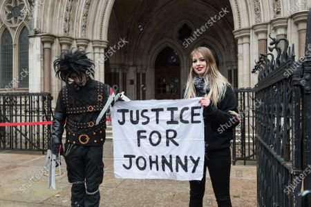 Johnny Depp's supporters, one dressed as the movie character Edward Scissorhands (L), hold a banner outside the Royal Courts of Justice as Johnny Depp's legal team applies for permission to appeal, and to rely on further evidence in a bid to overturn last year's ruling in the libel claim against The Sun and its publisher News Group Newspapers over an article labelling him a wife beater, on 18 March, 2021 in London, England. The ruling by a High Court judge Mr Justice Nicol following a three-week trial in July last year found that the claims in the article were substantially true and that the US actor had assaulted his ex-wife Amber Heard.