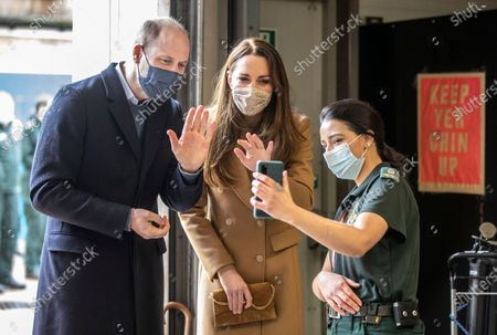 Stock Picture of Britain's Prince William and Kate Duchess of Cambridge talk with the family of paramedic Jahrin (Jay) Khan via a mobile phone, at Newham ambulance station in London, . The Khan family is in London but her father joined the conversation from Bangladesh, and Jahrin Khan has been unable to see her family throughout the pandemic. The royal couple talk with members of the ambulance service in the well being garden. The royal couple met with ambulance staff and paramedics about their experiences of working during the pandemic and about support for the mental health of health workers